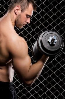Мощный парень с гантелями показывает мышцы на заборе