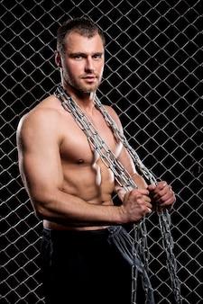 Мощный парень с цепью показывает свои мышцы