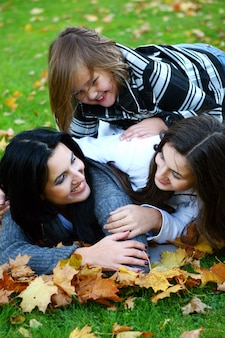 秋の公園を通って健康的な散歩を取る若い家族