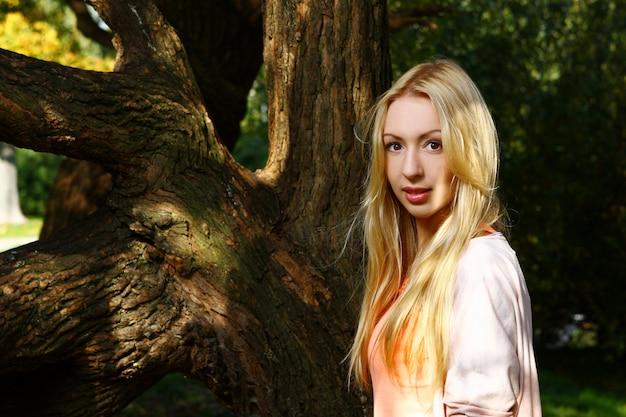 公園でポーズをとって若くて魅力的な女性