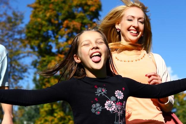 二人の幸せな姉妹が公園で楽しんでいます