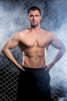 彼の筋肉を示すチェーンを持つ強力な男
