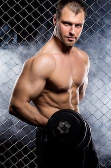 フェンスの上の筋肉を示すダンベルを持つ強力な男
