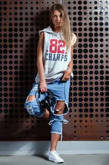 Красивая девушка в рваных джинсах