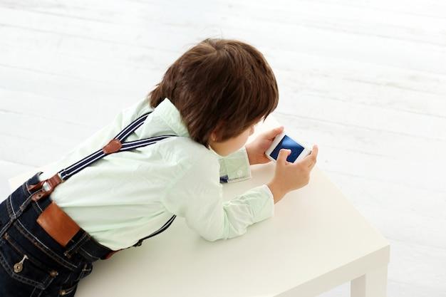 Прелестный ребенок играет со смартфоном