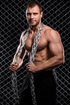 Сильный человек на заборе с цепями