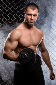 Сильный человек на заборе с гантелей