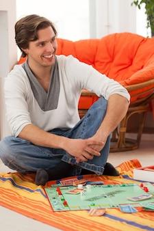 若い男が自宅でゲームをプレイ