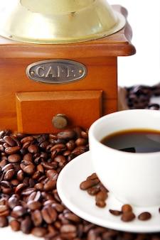 Старая кофемолка с белой чашкой
