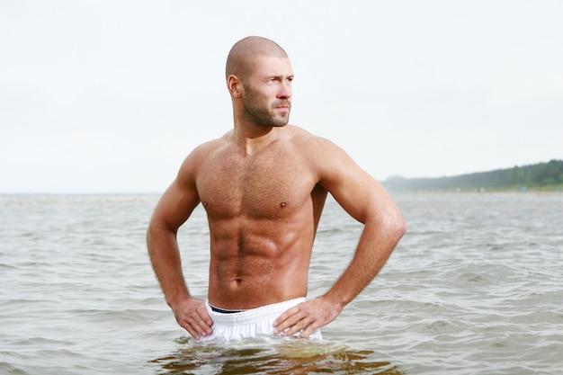 ビーチで魅力的で幸せな男