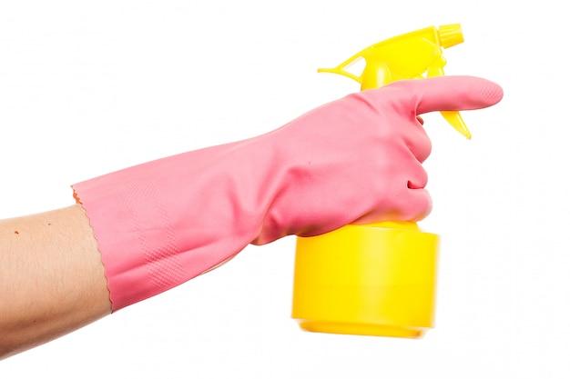 スプレーボトルを保持しているピンクの手袋で手します。