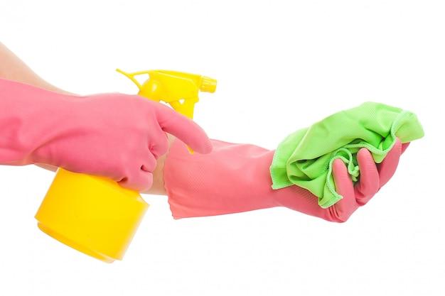 スプレーとスポンジを保持しているピンクの手袋で手します。