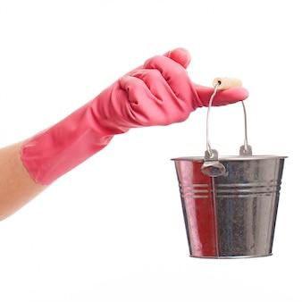 銀のバケツを保持しているピンクの手袋で手します。