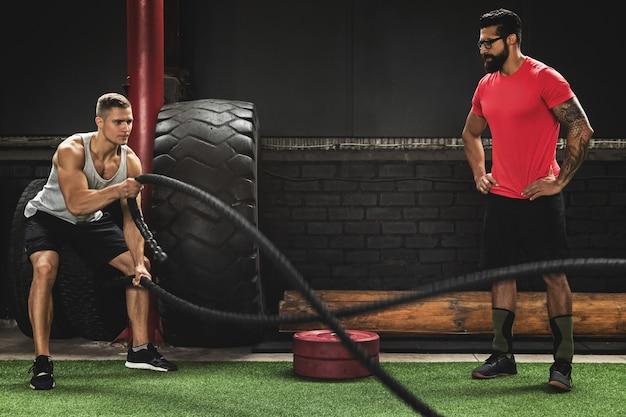 バトルロープ演習-彼のトレーナーと一緒にワークアウトする若いスポーツマン