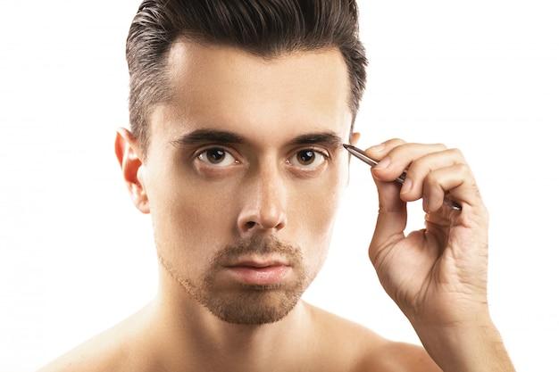 若い男が眉の近くにピンセットを持って、形状を修正します