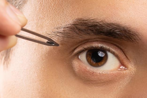 眉の形を矯正する男性の目とピンセット