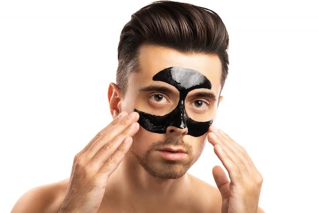 Молодой парень с черной угольной маской на лице на белом.