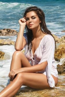 濡れたチュニックの女性が岩のビーチでポーズをとってください。