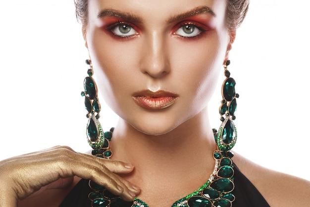 大きな美しいネックレスと多くの宝石とイヤリングを着ている女性