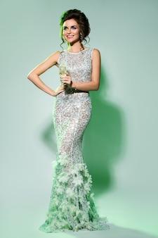 Великолепная женщина в красивом платье с бокалом шампанского