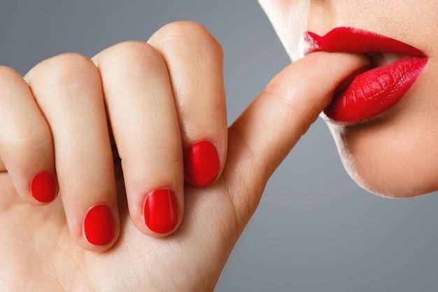 女性の口と赤いマニキュアと口紅の爪。