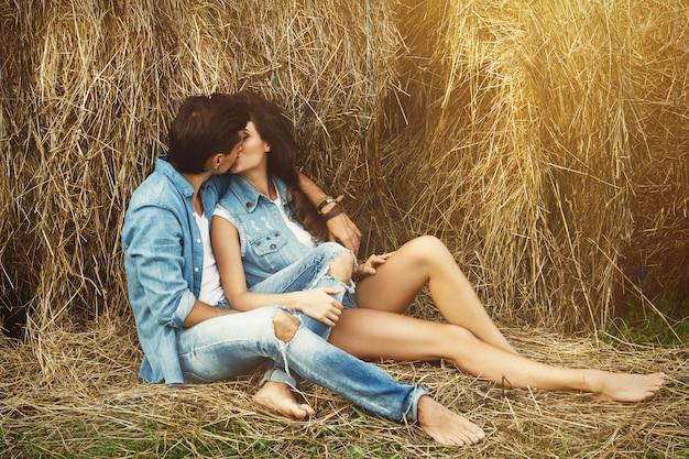ジーンズの服と干し草の山の若いカップル