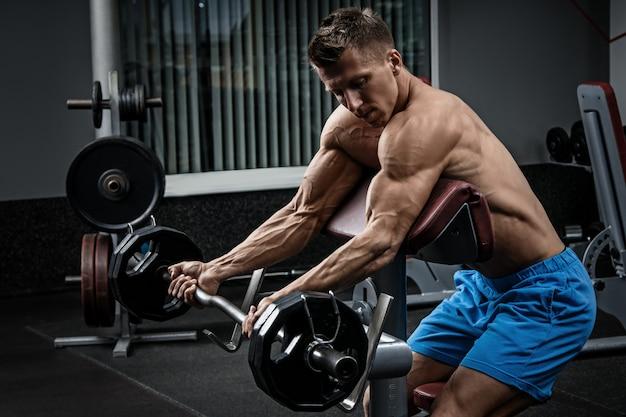 Мускулистый мужчина тренирует руки