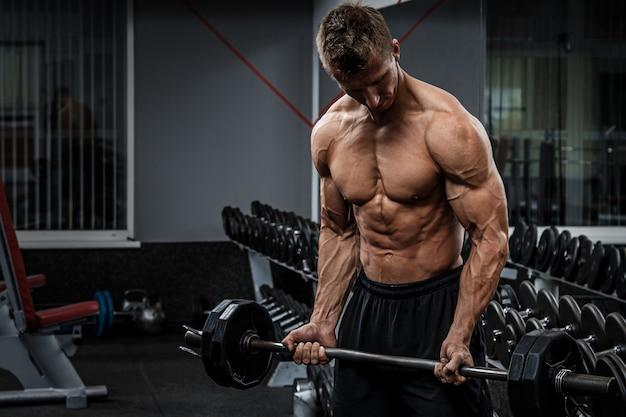 Мускулистый парень тренирует руки
