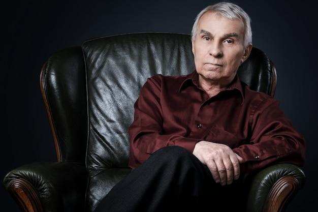 肘掛け椅子の年配の男性