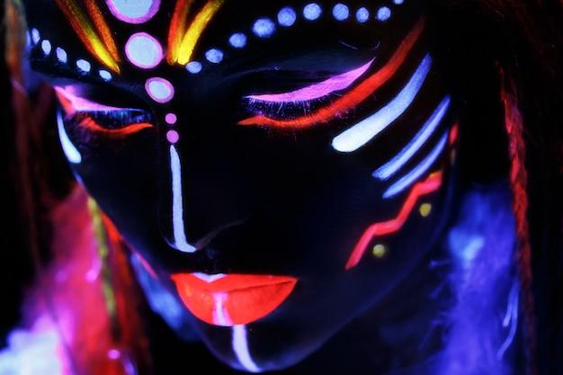 Женщина с неоновым макияжем в ультрафиолетовом свете
