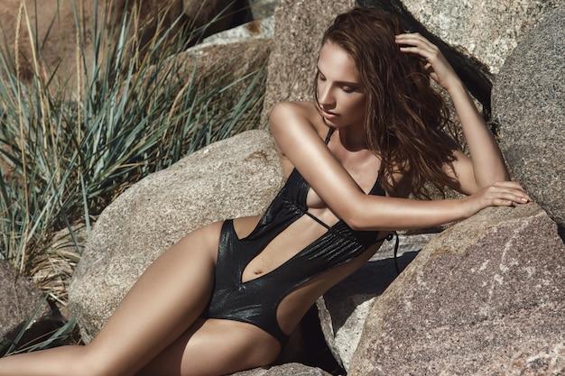 岩とビーチで美しい女性