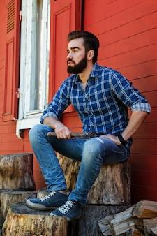 切り株に座っているハンサムなひげを生やした男