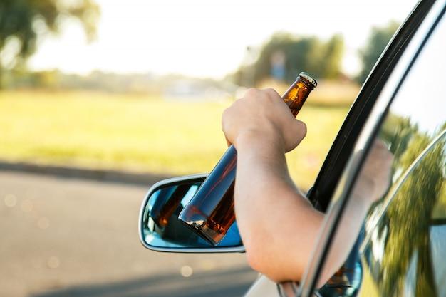 Водитель автомобиля держит бутылку пива