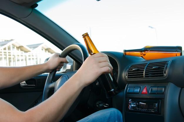 ビールのボトルを保持している車の運転手