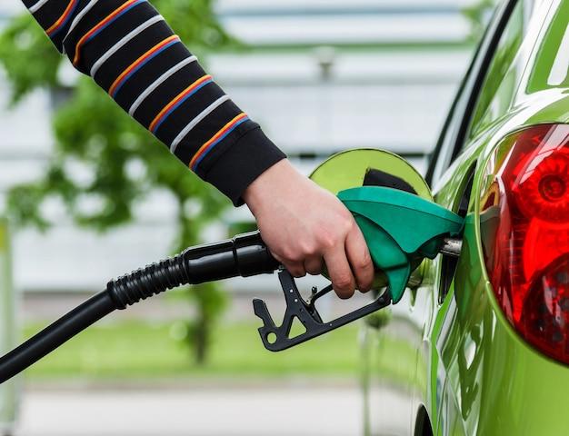 Человек заправляет свою машину бензином
