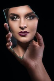 反射の女性の顔を持つ鏡の破片