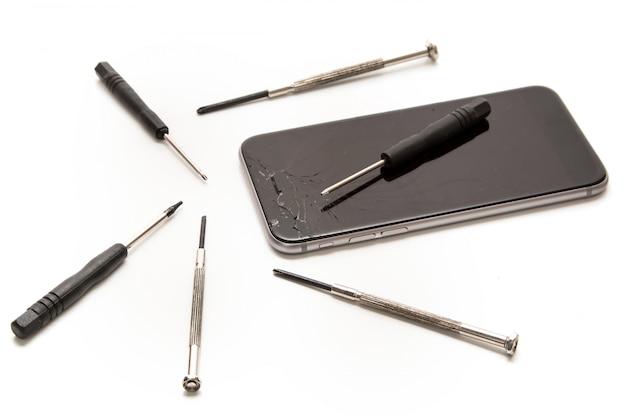 Сломанный смартфон и маленькие отвертки для ремонта