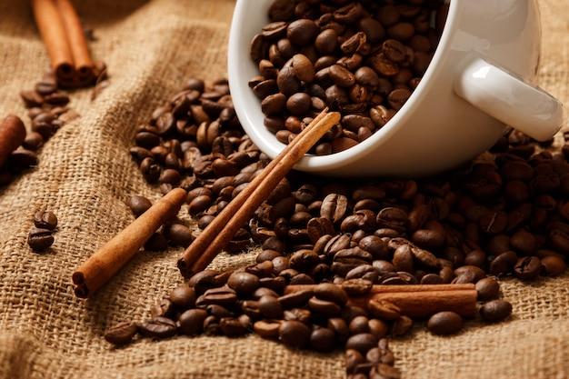 Чашка, кофейные зерна и палочки корицы