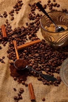 Жареный кофе в зернах и совок с молотым кофе