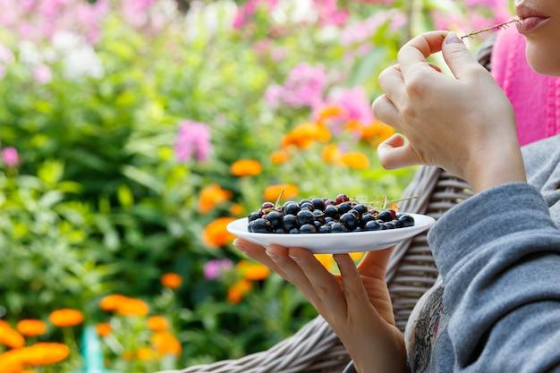 Женщина ест черную смородину