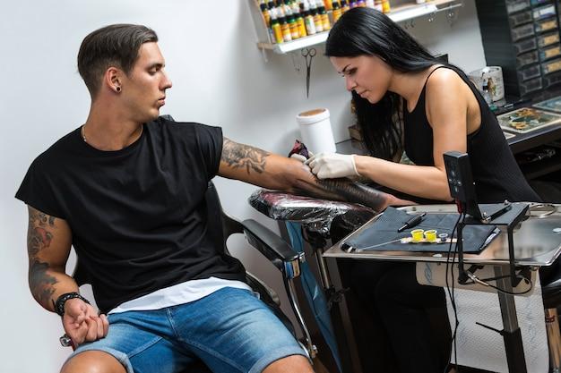 彼女の仕事中のタトゥーアーティスト