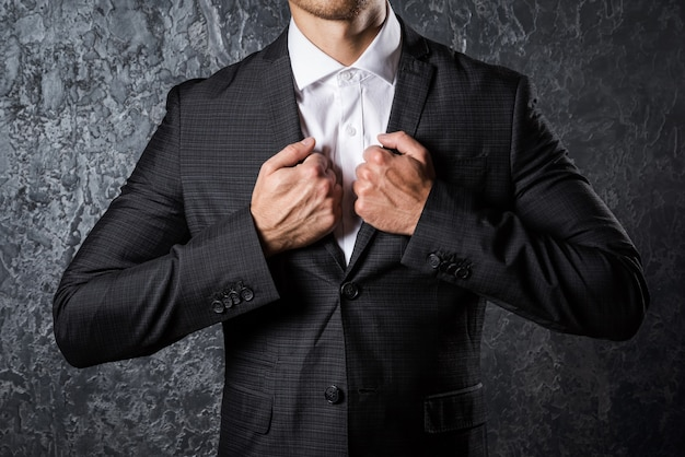 Человек в костюме против бетонной стены