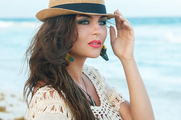 ビーチで帽子をかぶっている美しい女性