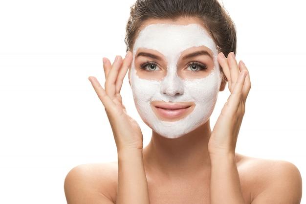 顔のマスクを持つ美しい女性