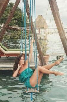水の上のブランコに乗っている美しい女性