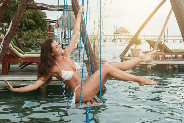 水の上にあるブランコに乗っている美しい女性