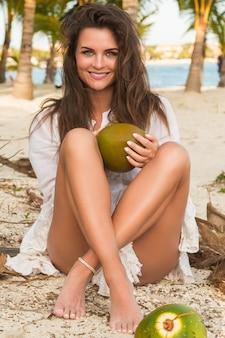 女性と地面にたくさんのココナッツ