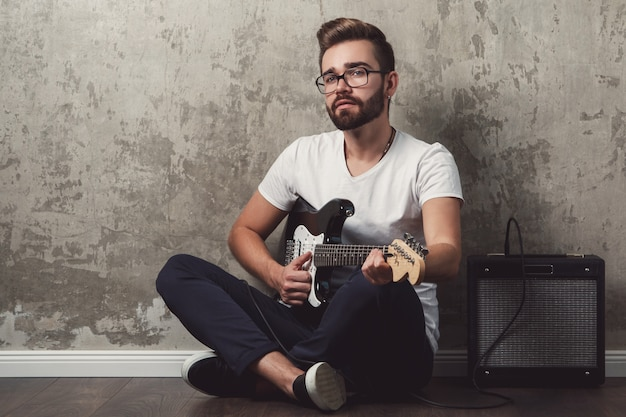 ギターを持つスタイリッシュな男