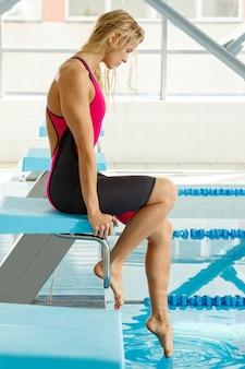 プールの横に座っている女子水泳選手