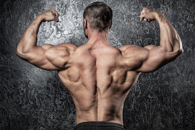 彼の筋肉の背中を示す男
